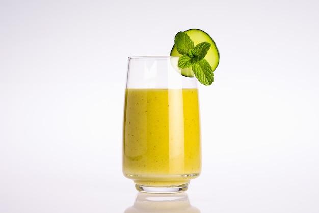 Copo de suco de vegetal orgânico verde e amarelo com fatia de pepino e folha de hortelã no fundo branco
