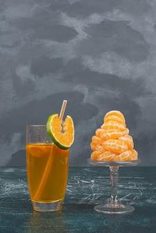 Copo de suco e fatias de tangerina na parede de mármore.