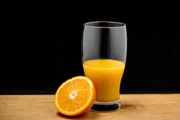 Copo de suco e meia laranja na mesa de madeira