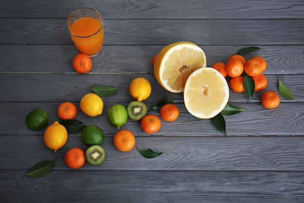 Copo de suco, metades de pomelo e frutas cítricas frescas na mesa de madeira