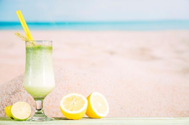 Copo de suco verde fresco e fatias de frutas cítricas