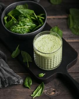 Copo de suco verde saudável caseiro com espinafre fresco em fundo escuro. alimentos e bebidas, dieta e conceito de alimentação saudável
