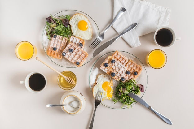 Copo de suco; xícara de chá; querida; leite em pó e prato de waffles; ovos fritos com salada no pano de fundo branco