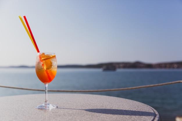Copo de swizzle de rum fica na mesa perto do mar