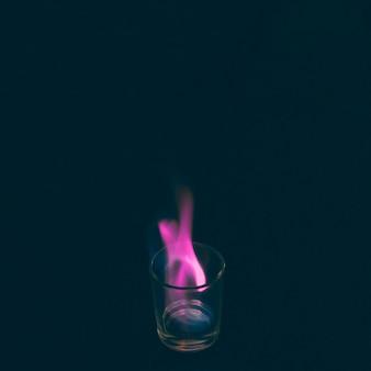 Copo de tequila queimando com chama rosa