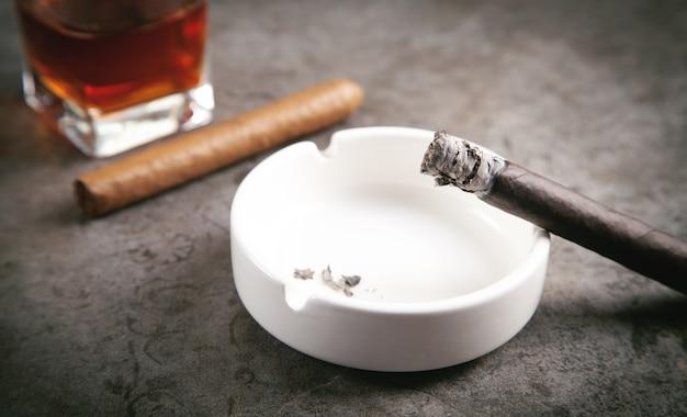 Copo de uísque, cinzeiro e charutos em cima da mesa.