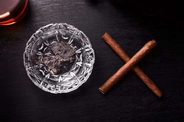 Copo de uísque com charuto de fumar.