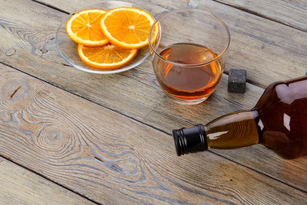 Copo de uísque com corte de frutas laranja