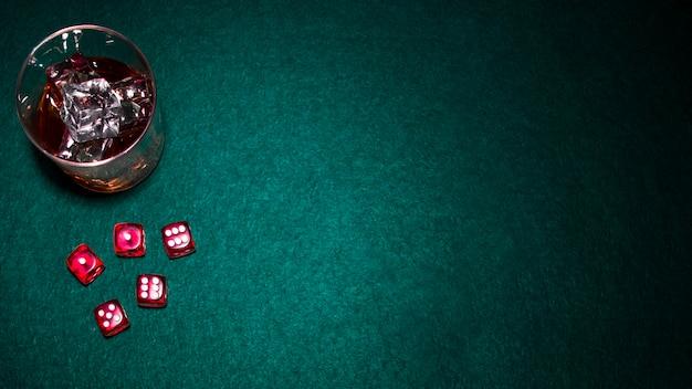 Copo de uísque com cubos de gelo e dadinhos vermelhos sobre fundo verde poker
