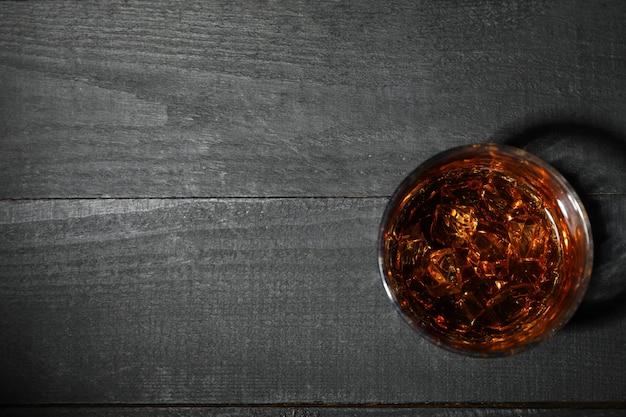 Copo de uísque com cubos de gelo no escuro de madeira