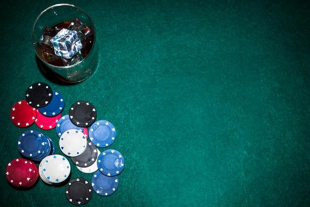 Copo de uísque com cubos de gelo sobre a mesa de jogo