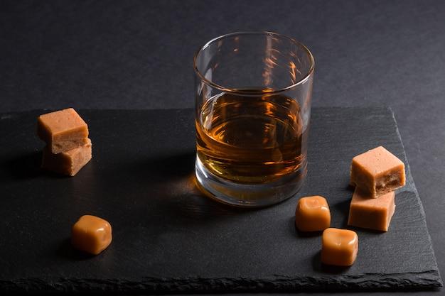 Copo de uísque com doces de caramelo em uma placa de ardósia de pedra preta. vista lateral