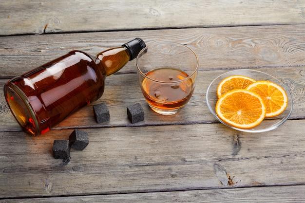 Copo de uísque com frutas laranja cortadas no fundo escuro de madeira