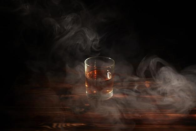 Copo de uísque com fumaça e gelo em uma mesa de madeira