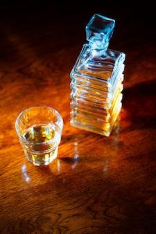 Copo de uísque com jarra quadrada velha em uma mesa de madeira envernizada
