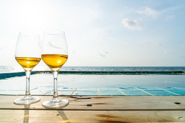 Copo de uísque com piscina e mar