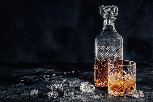 Copo de uísque com uma garrafa quadrada em um fundo de pedra preta.