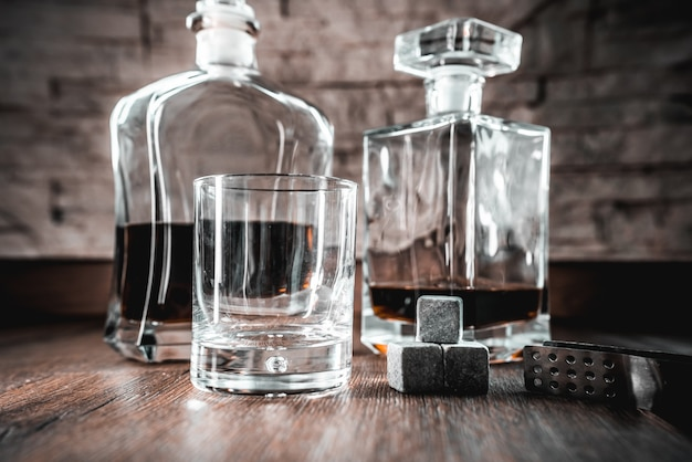 Copo de uísque com uma garrafa sobre uma mesa de madeira e pedras de resfriamento de gelo.