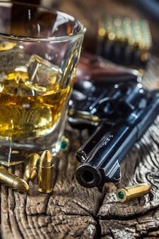 Copo de uísque conhaque ou bourbon com revólver e balas na mesa de madeira.