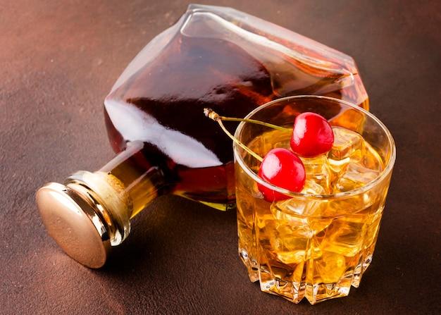 Copo de uísque de ângulo alto e cerejas com garrafa