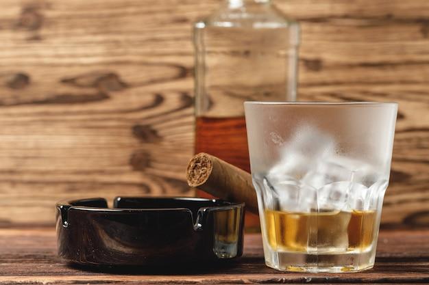 Copo de uísque e charutos enrolados na mesa de madeira