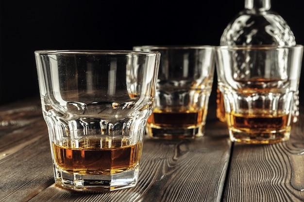 Copo de uísque e garrafa na mesa de madeira velha