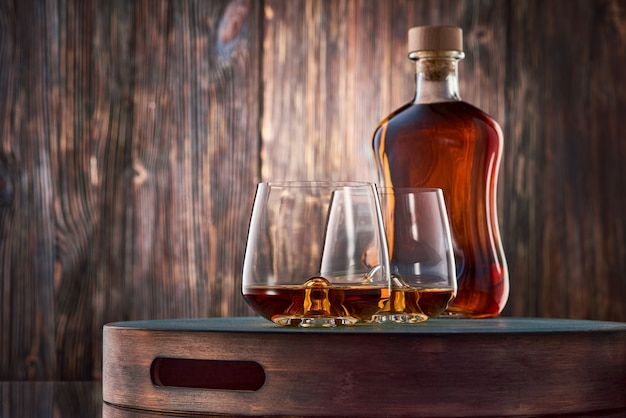 Copo de uísque e uma garrafa na mesa de madeira