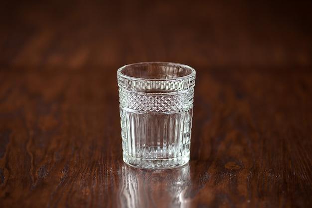 Copo de uísque elegante na mesa de madeira escura