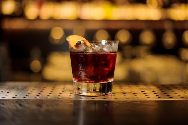Copo de uísque fresco e forte cocktail decorado com casca de laranja