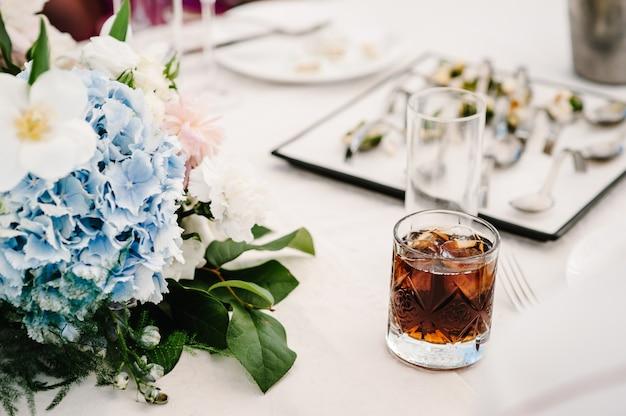 Copo de uísque, uísque com cubos de gelo em uma mesa rústica festiva