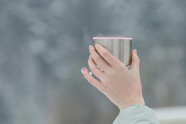 Copo de uma garrafa térmica com bebida fumegante em uma mão feminina em um fundo desfocado.