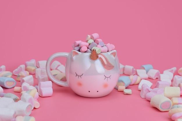 Copo de unicórnio dormindo em um fundo rosa com marshmallows misturados e lugar para texto. conceito de doces com espaço de cópia.