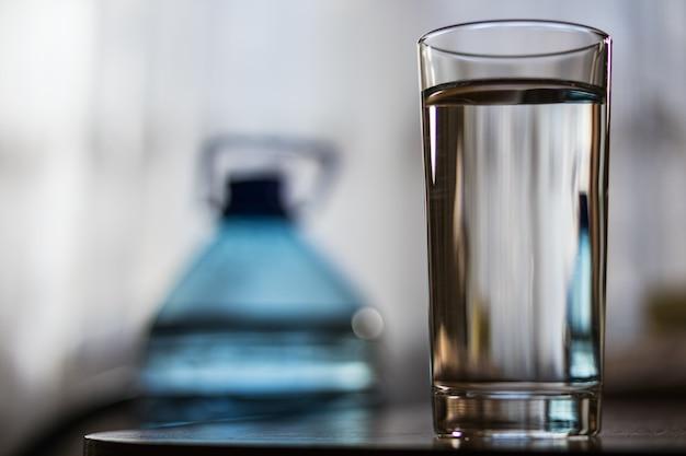 Copo de vidro com água e uma garrafa de plástico