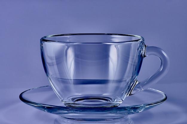 Copo de vidro com água sobre um fundo azul.