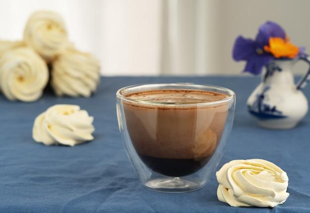 Copo de vidro com café com leite em cima da mesa, ao lado de marshmallows caseiros. flores da primavera em um vaso ao lado de zéfiro.