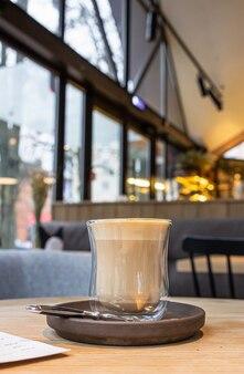 Copo de vidro com cappuccino na mesa de madeira no café