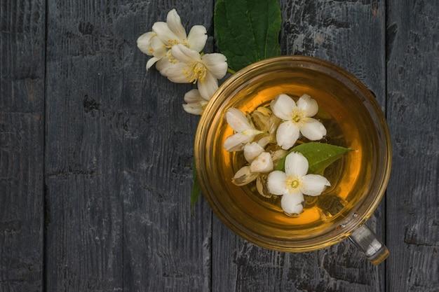 Copo de vidro com chá floral fresco e flores de jasmim em um fundo de madeira.