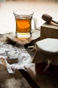 Copo de vidro com chá quente com pote de mel ou geléia, colher de madeira, polvoron de cookie espanhol na caixa vintage