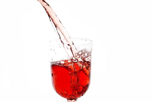 Copo de vidro com derramar suco em um plano de fundo branco