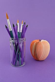 Copo de vidro com lápis e pincéis em fundo violeta com maçã vermelha falsa