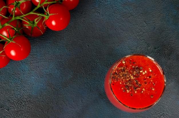 Copo de vidro com suco de tomate com pimenta preta e tomate cereja no escuro