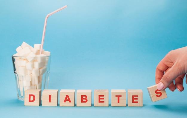 Copo de vidro com um canudo cheio de cubos de açúcar branco. letras maiúsculas de diabetes em palavras cruzadas.