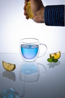 Copo de vidro de anchan azul orgânico na mesa de luz. chá de ervas