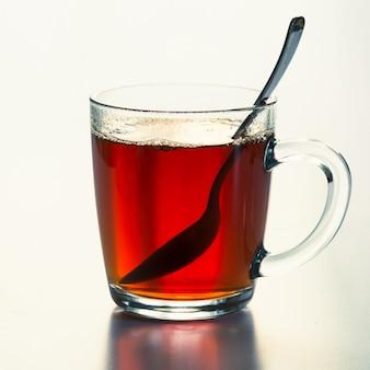 Copo de vidro de chá preto quente em branco.