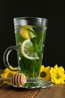 Copo de vidro do chá da hortelã com fatias do limão, fundo escuro.