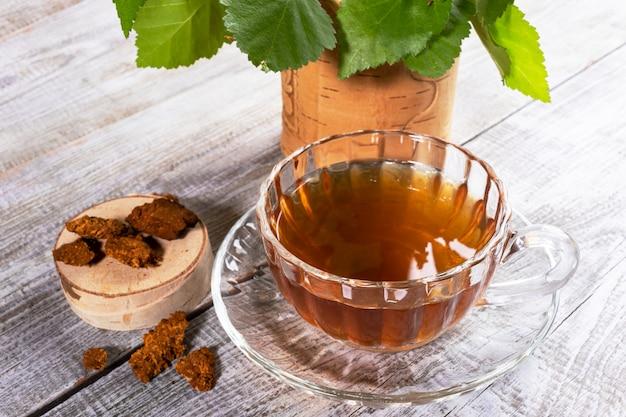 Copo de vidro do chá de chaga de cogumelo de vidoeiro no close up de madeira da tabela.
