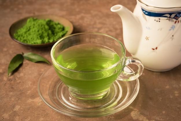 Copo de vidro do chá quente com pó do chá verde e bule na tabela.