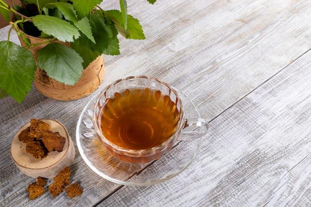 Copo de vidro figurado de cura infusão de bétula chaga com pedaços de chaga e folhas na mesa de madeira.