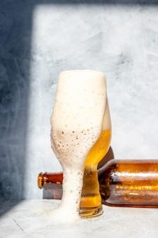 Copo de vidro servido com cerveja ipa e uma garrafa e uma lata no fundo