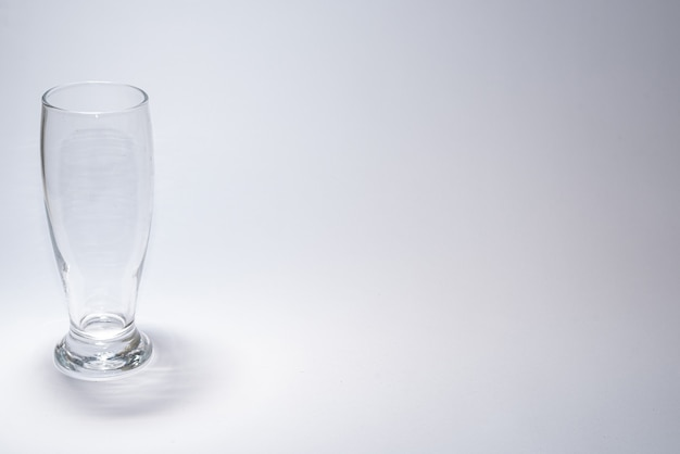 Copo de vidro tradicional sobre mesa branca com copyspace